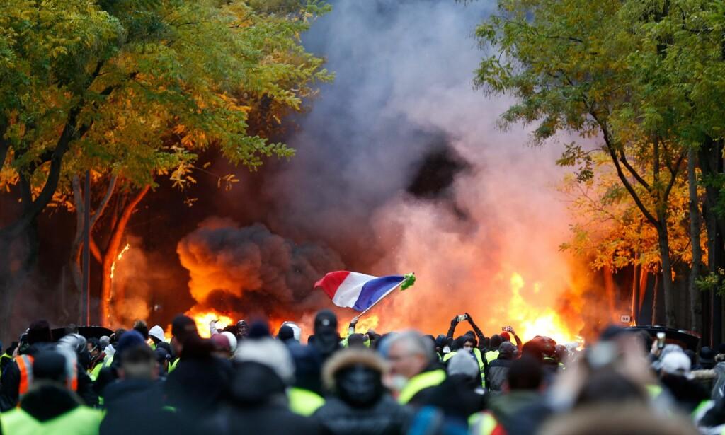 - TENTE PÅ BYGG: Mange biler ble satt i brann lørdag, og noen demonstranter tente også på en bygning langs paradegaten Champs-Élysées, ifølge nyhetsbyrået Reuters. Foto: AFP / NTB Scanpix