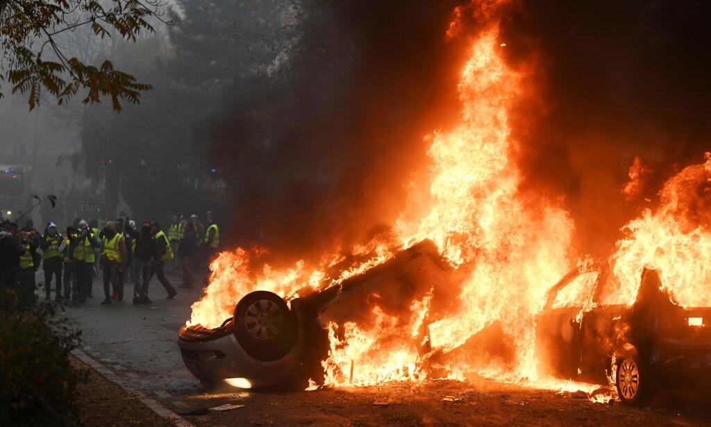 BILBRANN: Demonstranter er avbildet ved siden av flere brennende biler under lørdagens demonstrasjoner i Paris. Foto: AFP / NTB Scanpix