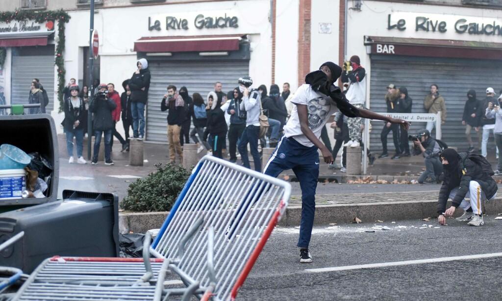 En ung mann kaster en ukjent gjenstand mot politiet i Pont Neuf, i Toulouse, sør i Frankrike, torsdag 6. desember. Foto: Remy Gabalda / AFP