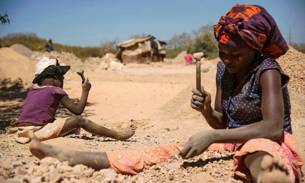 SYKDOM: Dette bildet fra mai 2016 viser et barn og en kvinne som knuser steiner hentet ut fra en koboltgruve i Lubumbashi, der gruvedriften skal ha ført til forurensning og sykdom. Foto: Junior Kannah / AFP / NTB Scanpix