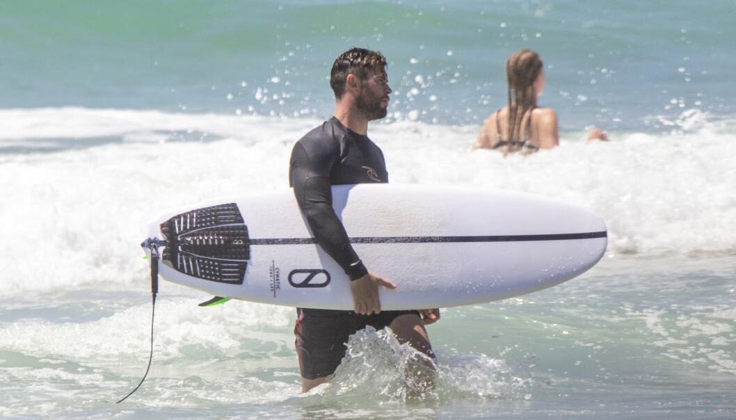 SPORTY: Chris Hemsworth er glad i å bevege seg, og når han ser en mulighet til å surfe tar han den på strak arm. Foto: NTB Scanpix