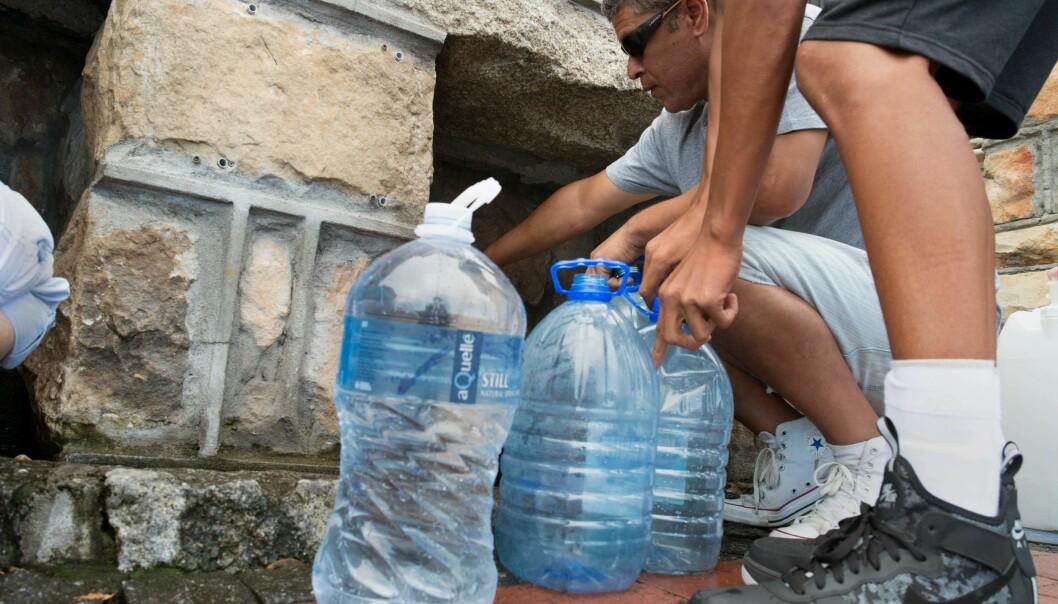 VANNMANGEL: Folk hentet vann fra kraner i gatene i Cape Town. Ordføreren sa den 18. januar i år at folks vannforbruk måtte kuttes ned til femti liter om dagen. Foto: Rodger Bosch/ AFP Photo