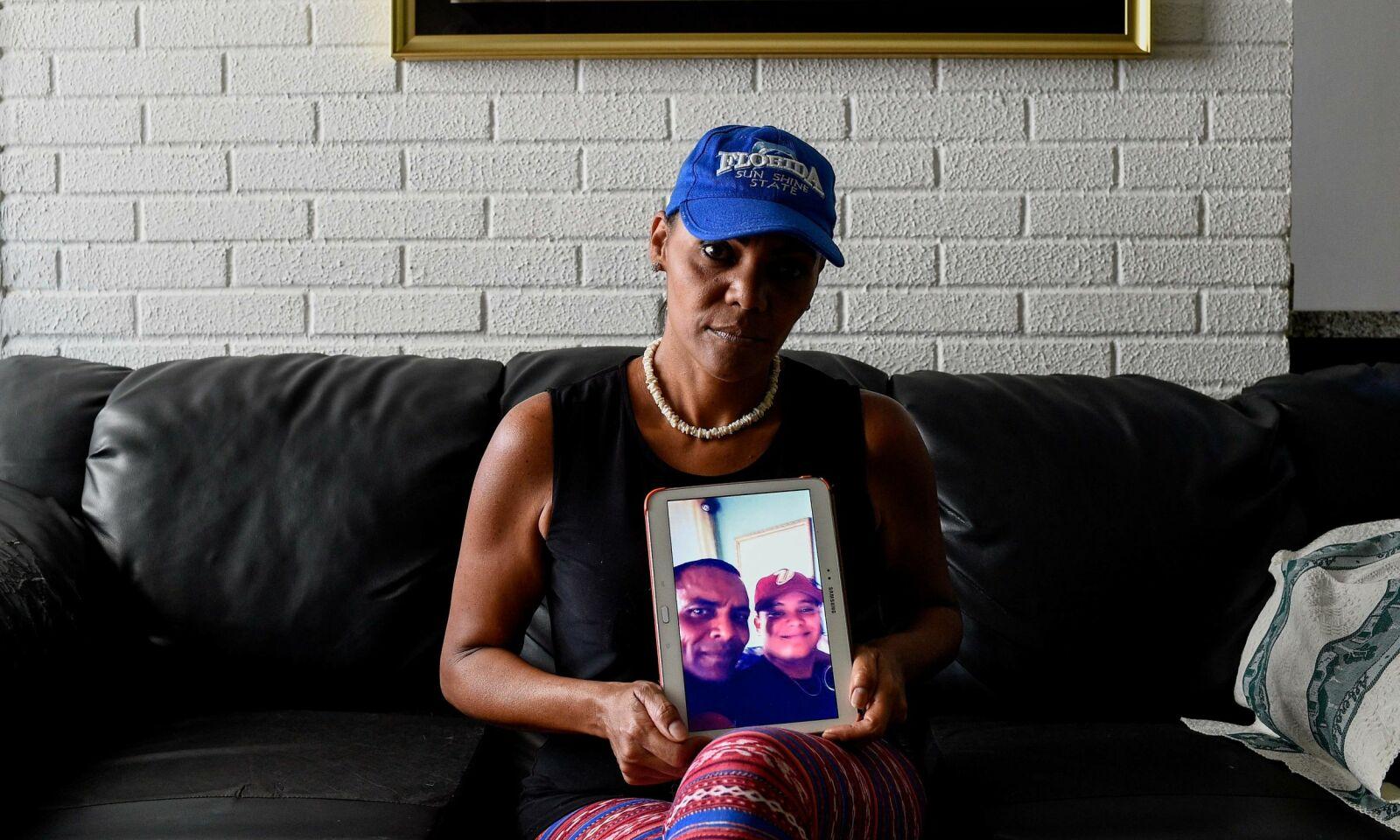 SITTER IGJEN: Yamileth Marcano viser fram et bilde av broren som ble drept av ranere som ville ta fra ham telefonen sin. Foto: AFP / NTB Scanpix.