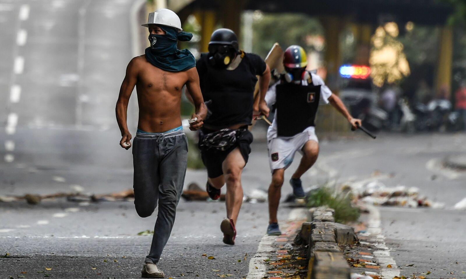 RØMMER: Her rømmer demonstranter fra opptøyer med politiet, etter en demonstrasjon mot president Nicolás Maduros regime. Foto: AFP / NTB Scanpix.
