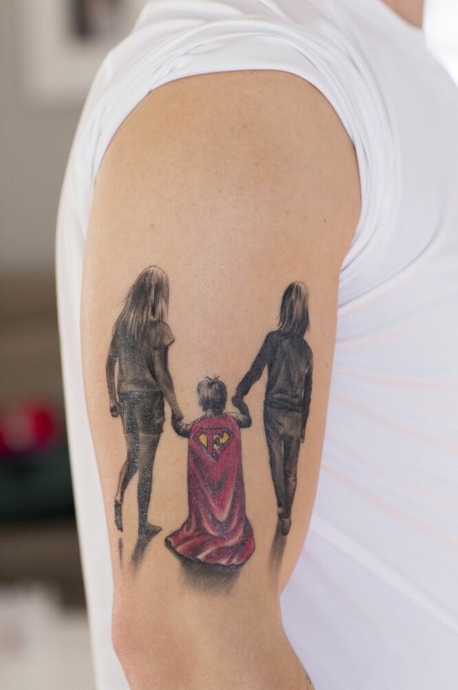 TATOVERING: På overarmen til pappa Niklas lyser en tatovering: Døtrene som går bortover veien, med en gutt i supermannkappe mellom seg. «E» for Elliot står det på kappen. FOTO: Charlotte Wiig