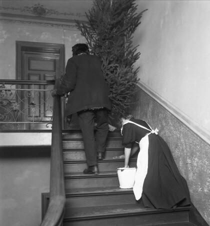 TRAPPEVASK: Bybudet kommer med juletreet for 1909 mens hushjelpen tar trappevasken i en bygård på Frogner i Oslo. FOTO: Anders Beer Wilse / Oslo Museum