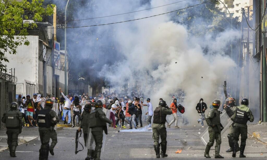 OPPTØYER: Opprørspolitiet brukte tåregass og gummikuler mot demonstranter under en protest mot president Nicolás Maduro 23. januar. Foto: Yuri Cortez / AFP / NTB Scanpix