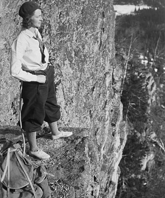 En dame avbildet på Kolsåstoppen en gang mellom 1920-1940, iført pen skjorte og et slags slips eller tørkle rundt halsen. Fotograf: Peter Wessel Zapffe / Nasjonalbiblioteket