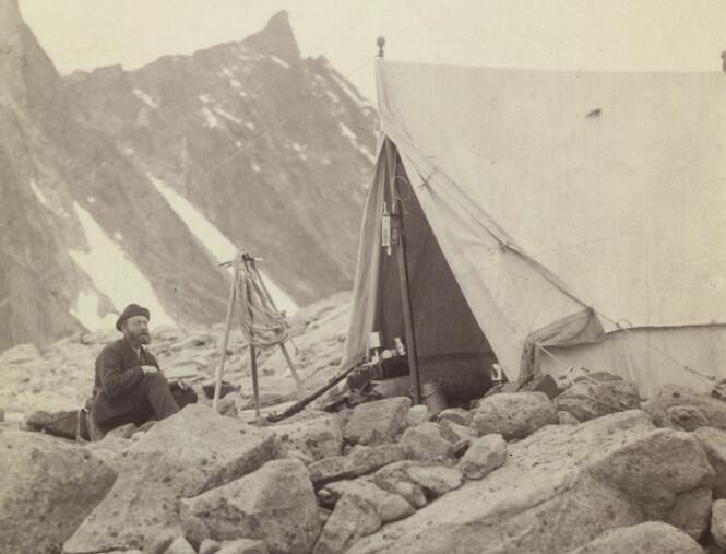 <strong>TELT:</strong> Torgeir Sulheim med hatt og frakk foran et telt på Store Skagastølstind, august 1887. Foto: Carl Christian Hall / Nasjonalbiblioteket