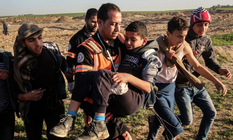 STRAFFEFRIDOM: Noreg gjev altså Israel straffefridom for deira brot på folkeretten. Dei vert heller lønna med auka økonomisk samarbeid, skriv innsendaren. Her bærer redningsarbeidere en ung, skadet gutt vekk fra demonstrasjoner ved grensa i Gaza, 4. januar i år. Foto: Said Khatib / AFP / NTB Scanpix
