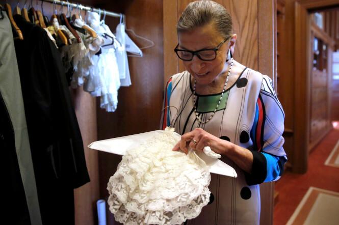 GÅR SINE EGNE VEIER: Ruth Bader Ginsburg har valgt å ikke bruke den tradisjonelle amerikanske dommerkappen, men heller gå for den franske varianten robe d'avocat med jabot (rysje) i halsen. Hun har en stor samling med jabots fra hele verden. Her viser hun frem en av dem. Bildet er tatt i 2016. FOTO: NTB Scanpix