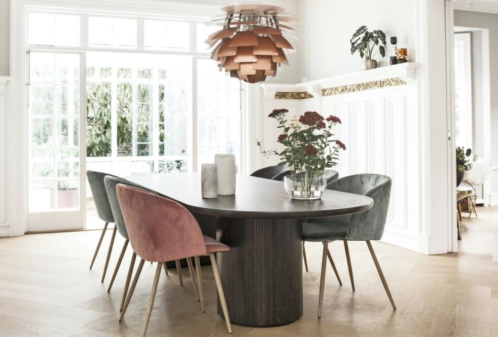 PERSONLIG STIL: Bruk ditt hjems arkitektoniske detaljer aktivt i innredningen. Den gullfargede stukkaturen blir framhevet av PHs «Konglelampe», og gulvet er lagt i et utradisjonelt sildebeinsmønster av planker fra Dinesen. Gulvteppet er fra Egetepper, spisebordet «Moon» er fra Gubi, spisebordsstolene fra Søstrene Grene, og «Ikebana»-vasen er fra Fritz Hansen. FOTO: Frederikke Lea Heiberg