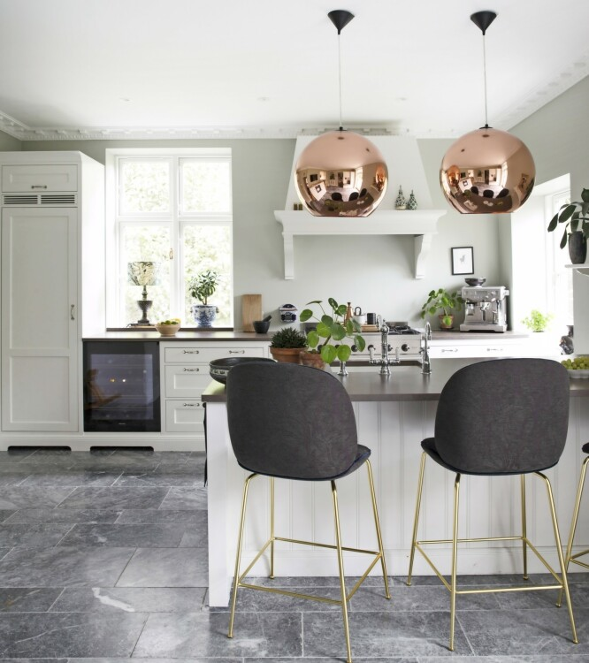Med behagelige barstoler og god belysning får man enkelt lyst til å henge ved bardisken. Kjøkkenet er fra Kvänum, gulvflisene heter «Bluestone», fra Klassiske fliser, mens barstolene er fra Gubi. Pendlene er fra Tom Dixon. FOTO: Frederikke Lea Heiberg