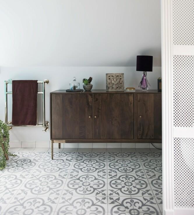 En skjenk i mørkt tre gjør badet hyggelig. Skjenken er fra Homeish, håndklevarmeren er fra Devon & Devon, og de marokkanske flisene fra Klassiske fliser. Vintagebordlampen i muranoglass er kjøpt hos Studio Septimius Krogh. FOTO: Frederikke Lea Heiberg