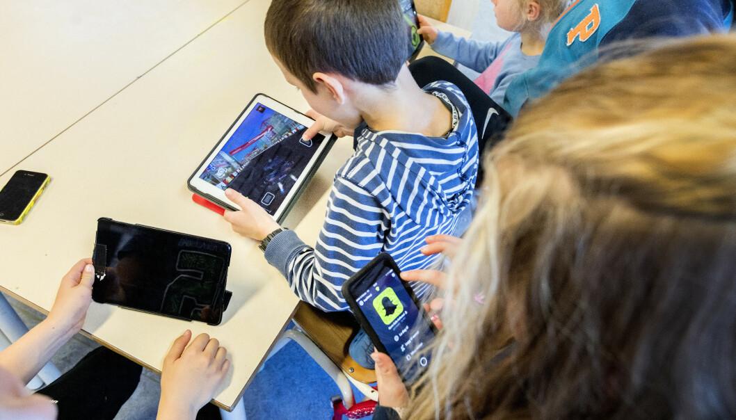 Elever som holder på med mobil og ipader i klassesituasjon på barneskole. Foto: Gorm Kallestad / NTB scanpix