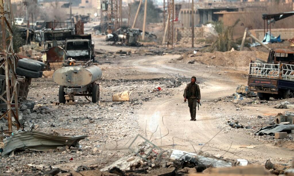 I RUINER: En soldat som kjempet med de kurdisledede opprørerne går gjennom ruinene i landsbyen Baghouz i slutten av januar. Etter en intens offensiv, er IS nå drevet ut av landsbyen. Foto: Delil SOULEIMAN / AFP / NTB Scanpix