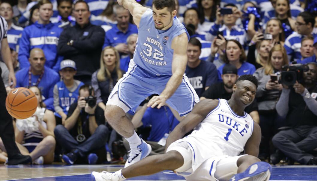 Supertalentet Zion Williamson vrir seg i smerter etter at basketballskoen hans revnet og han skadet kneet i onsdagens NCAA-storkamp mellom Duke og North Carolina. Hendelsen førte til at Nikes aksjekurs falt markant. Foto: Gerry Broome, AP / NTB scanpix