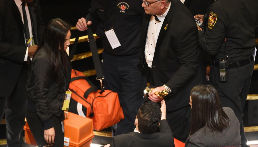 FALT: Rami Malek fikk hjelp av ambulansepersonell etter han falt på vei ned fra scenen. Foto: Chris Pizzello/Invision/AP