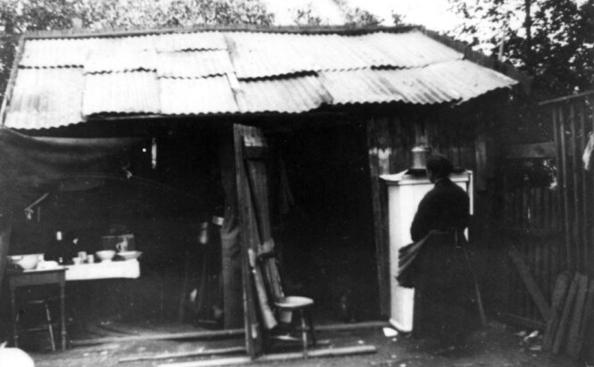 BODDE I SKUR: Nanna Broch fotograferte grelle boligforhold for arbeiderklassen, på denne måten gav hun mellomkrigstidens bolignød et ansikt. Her har hun tatt bilde av et skur som tilsynelatende fungerer som et hjem i 1920-årene. Foto: Nanna Broch / Norsk Folkemuseum.