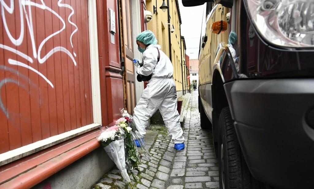 ÅSTEDET: Det var i andre etasje av dette trehuset i Prinsens gate i Trondheim at dobbeltdrapet fant sted i september i fjor. Her er en kriminaltekniker på åstedet. Utenfor huset satte folk opp blomster for å minnes de døde. Foto: Lars Eivind Bones