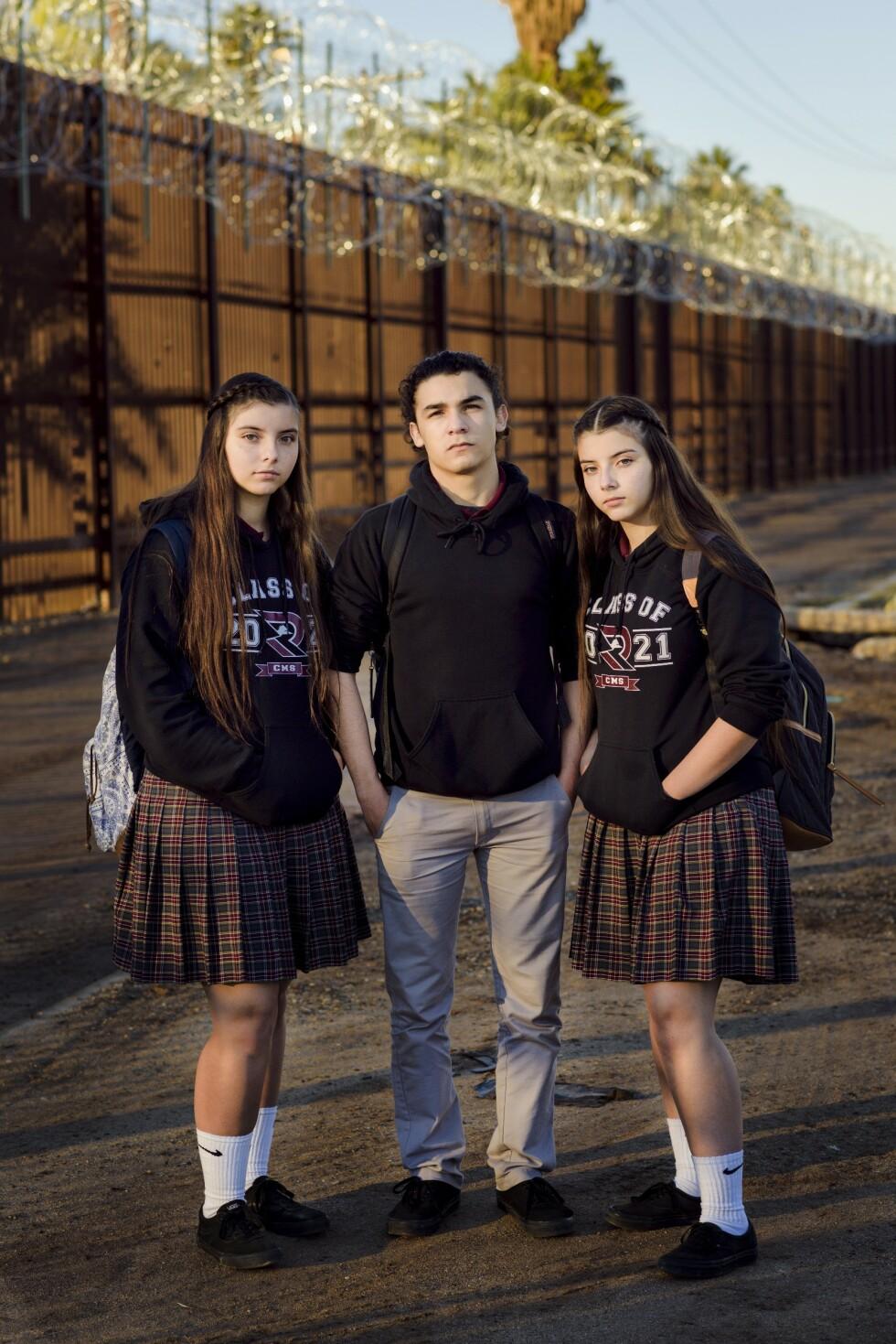GRENSELIV: Søsknene Ana Luisa (15), Patricio Bernal (17) og Ana Fernanda (15) foran grensegjerdet mot Mexico i byen Calexico, California, der de går på skole. På andre siden av grensegjerdet, ligger hjembyen Mexikali. Foto: Klaudia Lech