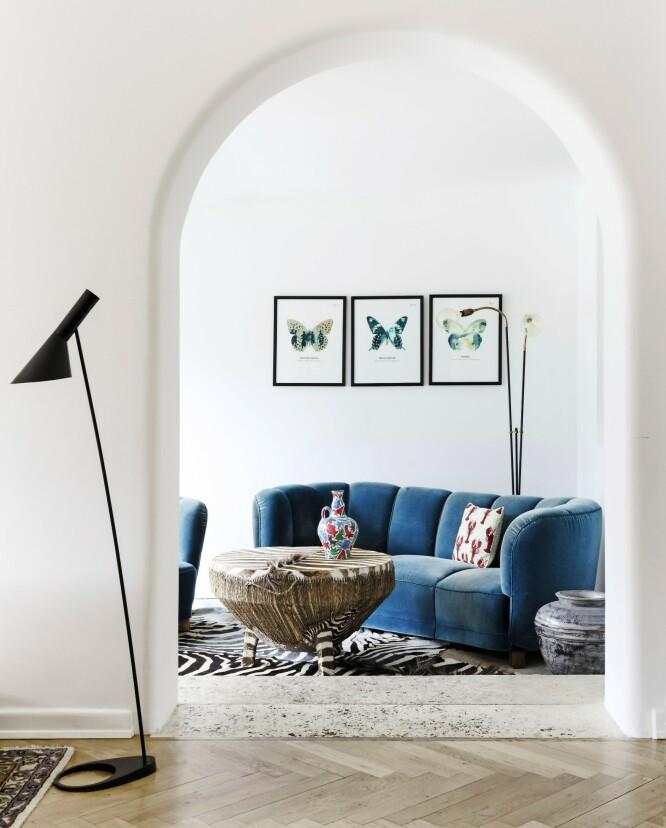 Fløyelssofaen er funnet på lauritz.com. De tre bildene med sommerfugler er laget av kunstner Peter Holst Henckel. Den store sebratrommen og lampen bak sofaen er kjøpt brukt. FOTO: Anitta Behrendt