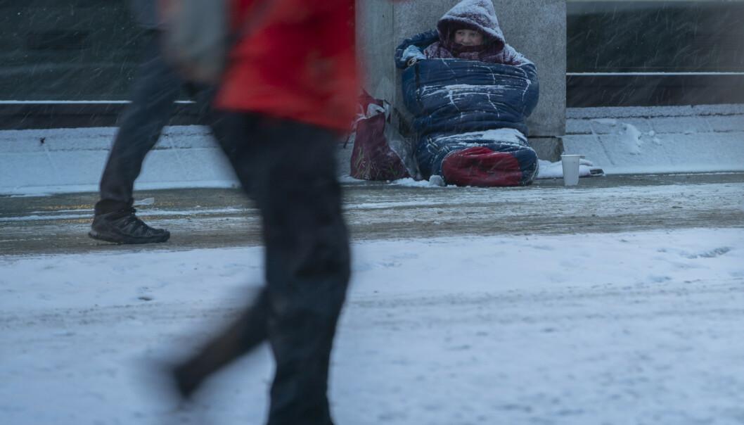 En rumensk tigger sitter i sin sovepose i snøværet på Karl Johansgate i Oslo. Foto: Heiko Junge / NTB scanpix