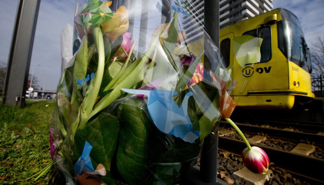 En trikk passerer blomsterbuketter lagt ned til minne om ofrene etter skytingen i Utrecht. Foto: AP Photo/Peter Dejong/NTB Scanpix