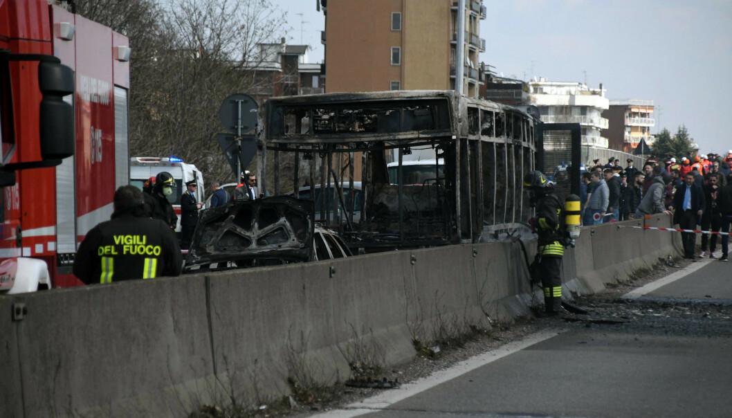 Brannvesenets mannskaper ved siden av det utbrente vraket av en skolebuss som skulle transportere barn fra Cremona i Lombardia-provinsen i Italia. Foto: AP / NTB scanpix.