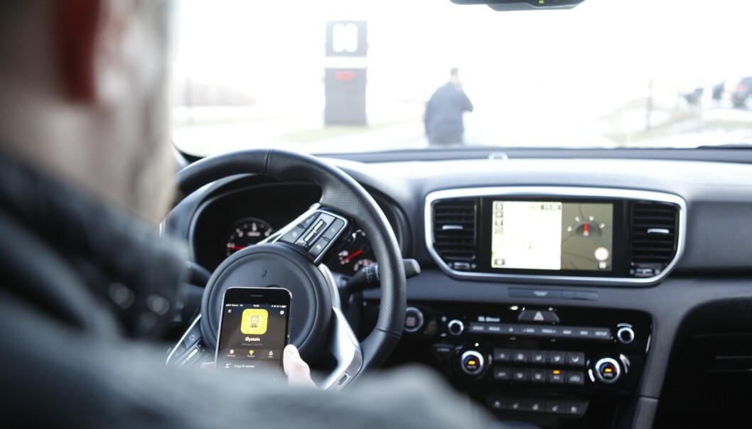 <strong>MOBIL I BIL:</strong> Er det straffbart å bruke mobilen på rødt lyst? Det skal Høyesterett avgjøre. Foto: Øystein Bergrud Fossum
