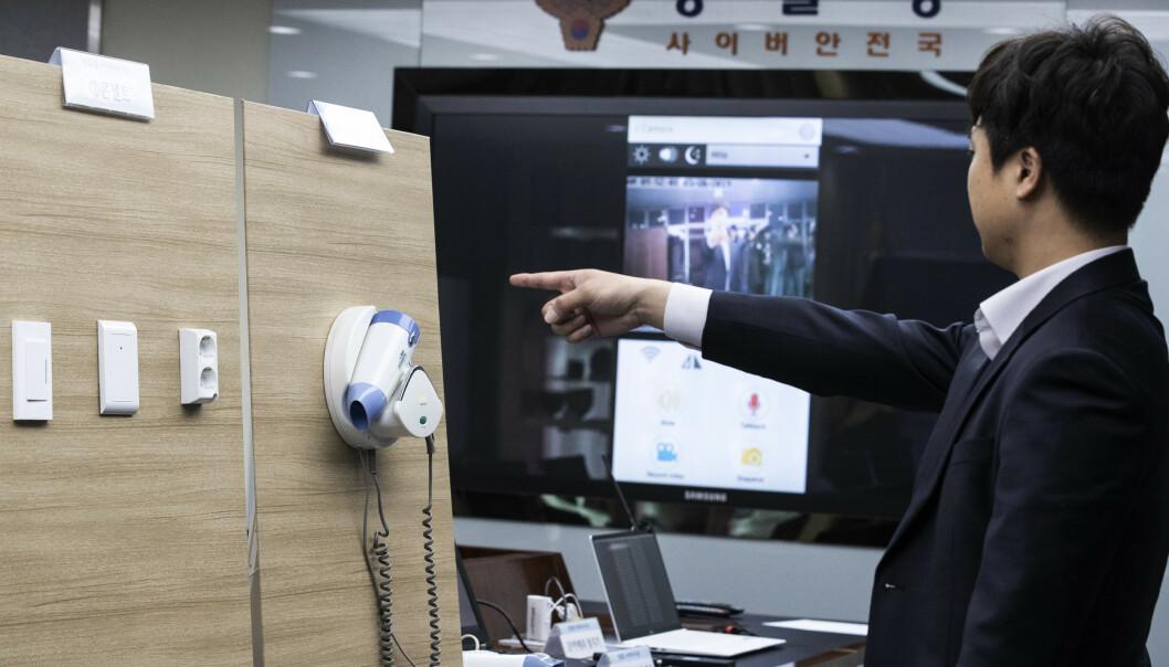 En sørkoreansk etterforsker demonstrerer et spionkamera installert i en hårføner, mens bildet fra kameraet vises på skjermen i bakgrunnen. Politiet i landet har pågrepet fire personer for å ha installert slike kameraer på hotellrom og lagt ut bildene på en nettside. Foto: Yun Dong-jin / AP / NTB scanpix