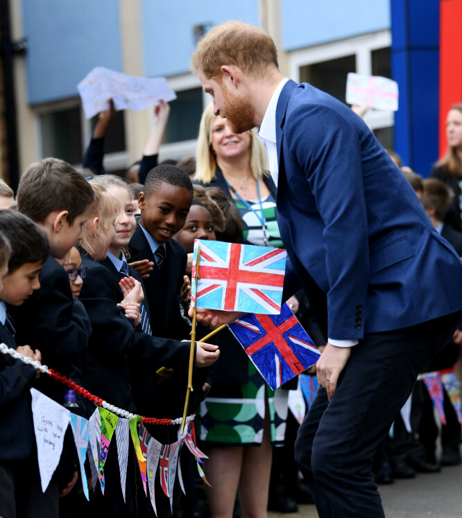 <strong>VARM VELKOMST:</strong> Flere av elevene fra skolen sto klare til å ta imot prins Harry med hjemmelagde flagg. Foto: NTB scanpix