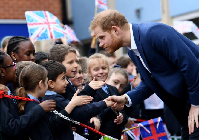 <strong>TOK SEG GOD TID:</strong> Den britiske prinsen tok seg god tid til å hilse på alle elevene som sto utenfor med flagg og velkomstskilt. Foto: NTB scanpix
