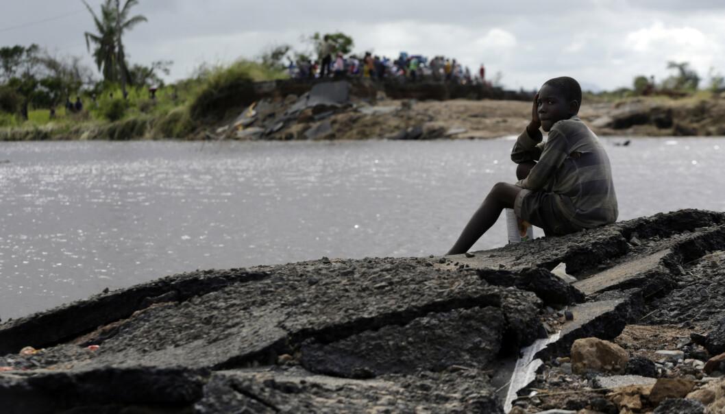 En ung gutt sitter ved restene av en bro som er ødelagt av vannmassene i Nhamatanda, rundt ti mil fra byen Beira i flomrammede Mosambik. Foto: Themba Hadebe / AP / NTB scanpix