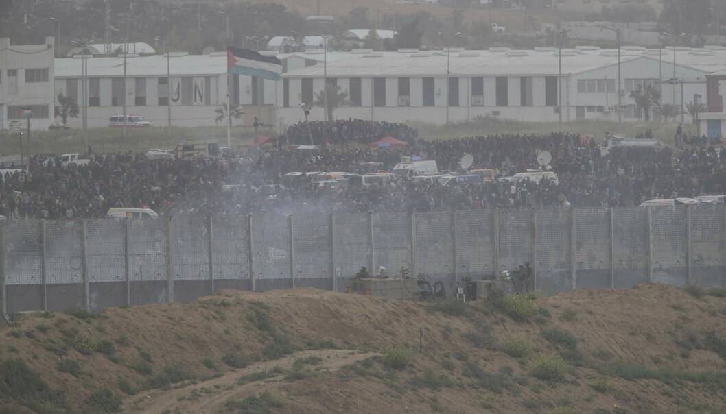 Israelske soldater og palestinske demonstranter ved grensegjerdet mellom Israel og Gazastripen lørdag. Foto: Tsafrir Abayov / AP / NTB scanpix