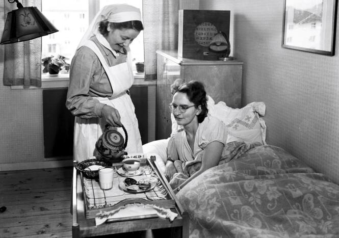 Husmorvikarordningen ble innført i 1929. Her får en syk kvinne servering ved sengen av en husmorvikar i 1950. FOTO: Leif Ørnelund/Oslo Museum