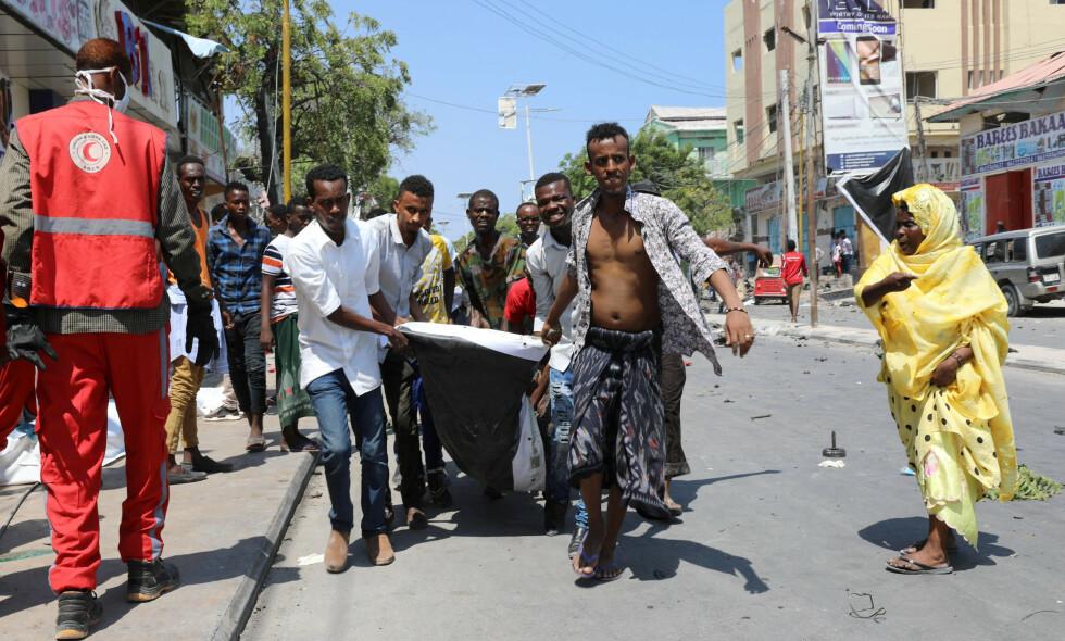 DREPT AV BILBOMBE: En mann fraktes bort etter å ha blitt drept av en bilbombe nær et hotell i Mogadishu, Somalia 28. mars. Kronikkforfatteren protesterer mot at norske myndigheter i økende grad returnerer somaliere til et Mogadishu som delvis ligger i ruiner. Foto: Feisal Omar / Reuters / NTB Scanpix