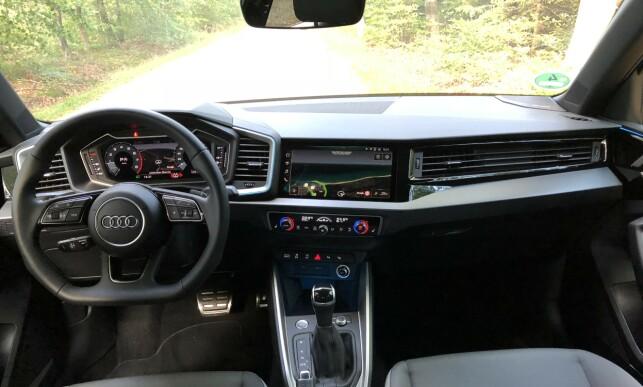 STILIG: Audi er rå på finish og detaljer. Skjermen er integrert og førerorientert. Virtuell cockpit (digital skjerm) koster 2.000 kr, men skal du ha den store multimediaskjermen og blåtannforbindelse til strømming, må du ha den mest avanserte navigasjonspakka, og må da ut med 26.000 ekstra. Foto: Rune M. Nesheim