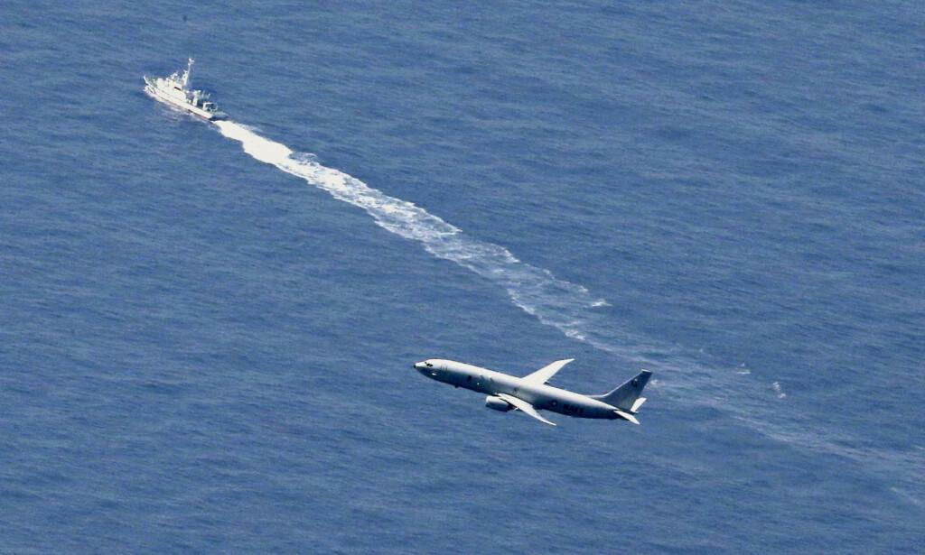 LETEAKSJON: Japansk kystvakt og et amerikansk fly søker etter vrakrestene. Redningsmannskaper har nå funnet vrakrester som tilhører flyet, sa en talsperson i militæret til nyhetsbyrået Reuters. Foto: Kyodo News/Reuters/NTB Scanpix