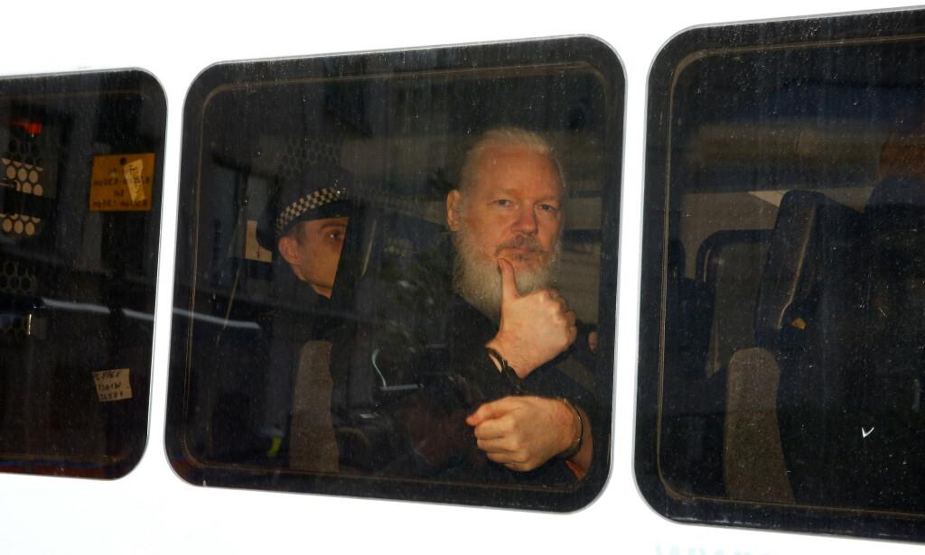 HER FRAKTES HAN BORT: Julian Assange ga tommel opp fra politibilen da han ble fraktet fra ambassaden der han ble pågrepet torsdag. Foto: Henry Nicholls / Reuters