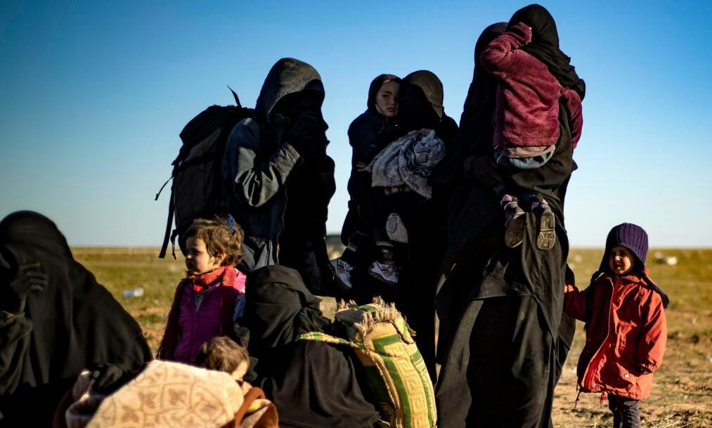 PÅ FLUKT: Kvinner og barn som har forlatt Den islamske statens siste skanse, Baghouz, venter på å bli undersøkt av medlemmer av syriske styrker øst i landet i mars. Noen av dem er norske. Skal de få reise hjem til Norge? Foto: Delil Souleiman / AFP / NTB Scanpix