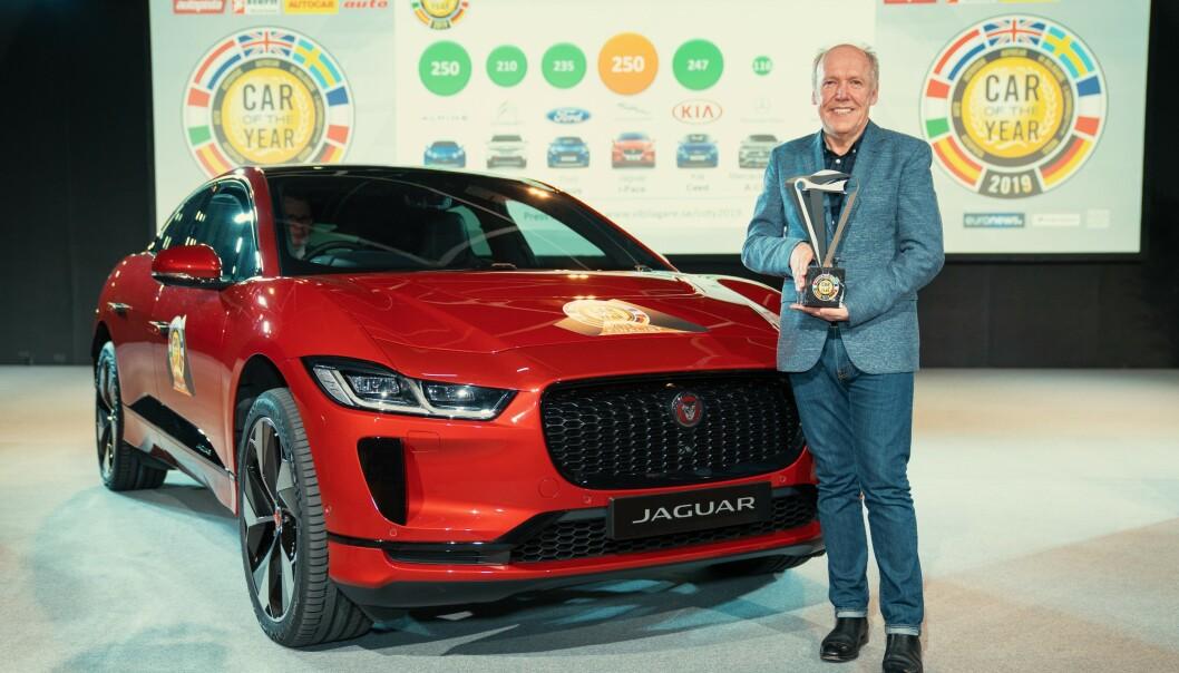 <strong>STOLT:</strong> Ian Callum kan stolt holde premien for å bli kåret til Årets Bil i Europa i Geneve i mars. Nå har han også tatt tittelen World Car of the Year og World Car design of the Year 2019. Foto: Jaguar