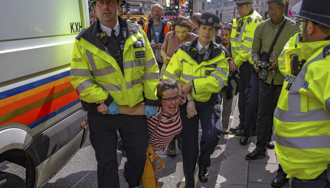 Politiet som arresterer demonstranter som blokkerer trafikken i London. Foto: AP Photo/Vudi Xhymshiti