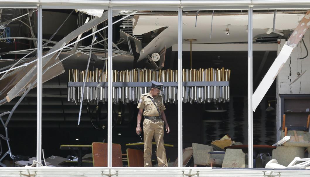 En politimann ser på skadene etter en av eksplosjonene som rammet et hotell i Colombo. Foto: AP / NTB scanpix