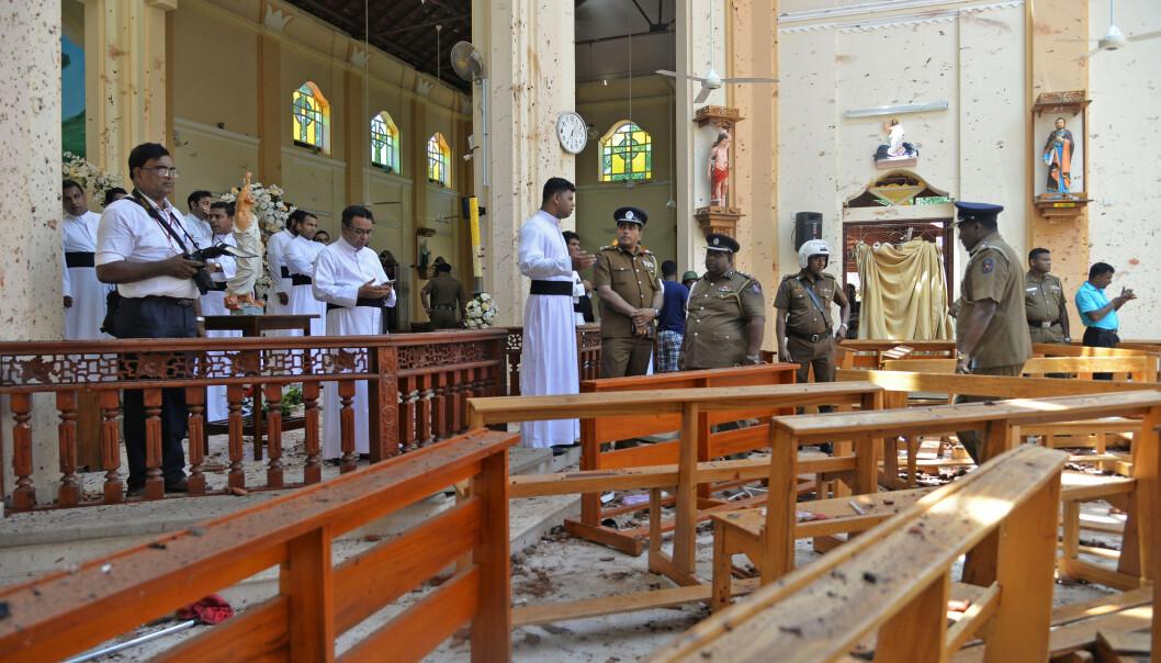 Polititjenestemenn og prester i en av kirkene som ble rammet av bombeangrep i Negombo, Sri Lanka. Foto: NTB scanpix /Reuters