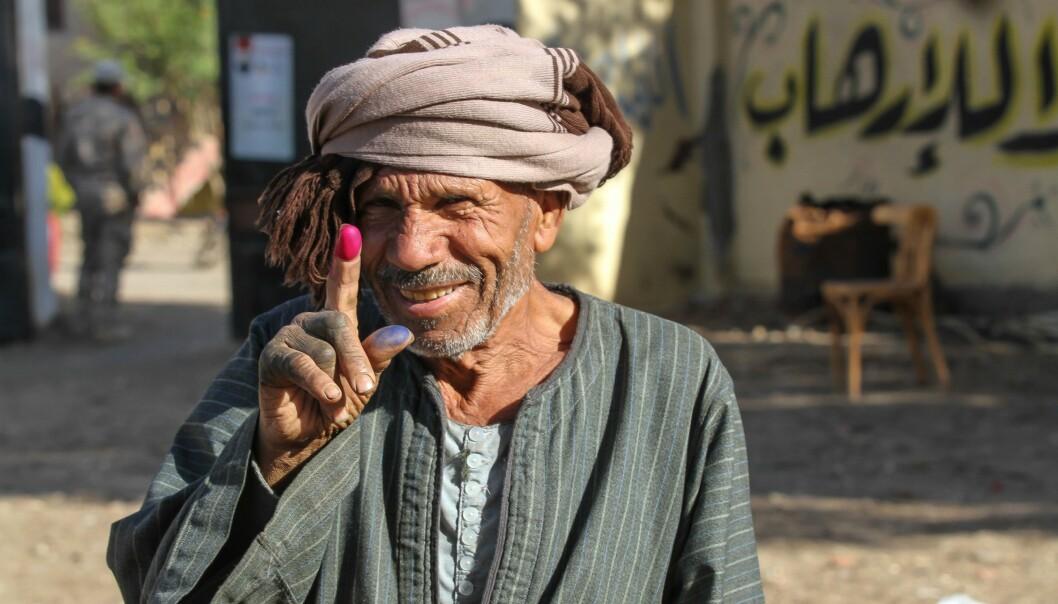BEVISET: En egyptisk mann viser fram fingeren som har fått stemme-blekk på seg, som viser at han har stemt under det pågående egyptiske valget. Den svært lite demokratisk innstilte presidenten Abdel Fattah al-Sisi ønsker å sitte fram til 2030, og ber nå om velgernes fullmakt til dette gjennom en referendum. Foto: Khaled Desouki / Afp / Scanpix