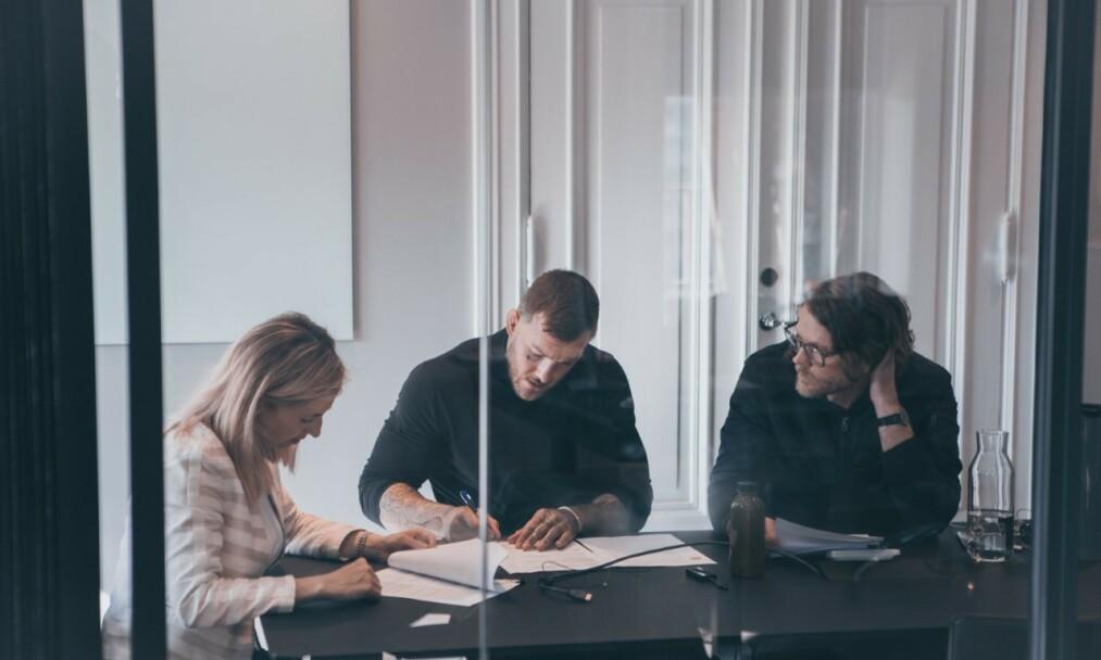 REISEN HAR STARTET: Kenneth Bergh signerer en omfattende bunke med dokumenter i kontrakten med mektige UFC. Med på møtet er jurist Karoline Bakalovic Kjeksli t.v. og manager Per Meland. Foto: Frederic Esnault, Face2Face Creatives
