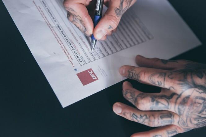 BLEKK OG TATOVERINGER: Kenneth Bergh setter sin signatur ved siden av UFC-logoen. Eventyret har startet. Foto: Frederic Esnault, Face2Face Creatives
