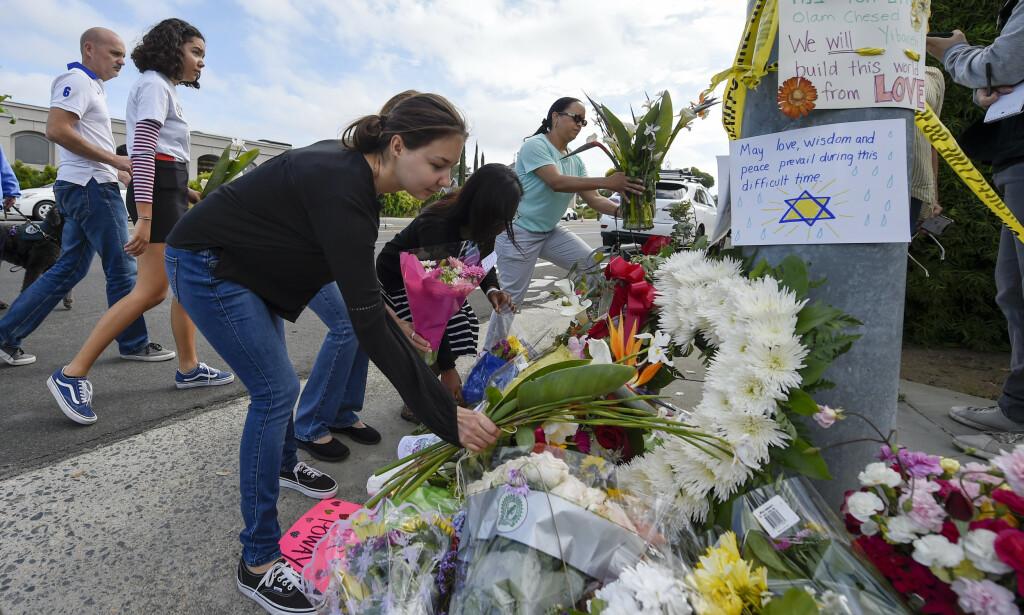 Folk legger ned blomster utenfor synagogen i Poway. En kvinne ble drept og tre personer såret i angrepet mot synagogen lørdag. Foto: Denis Poroy / AP / NTB scanpix