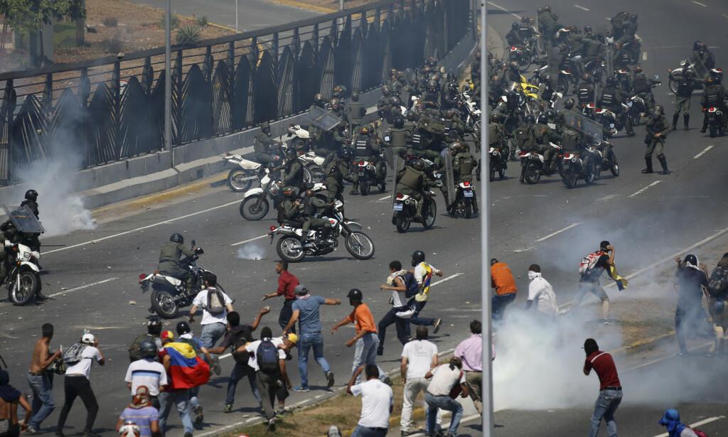 Bildet viser en konfrontasjon tirsdag mellom motstandere av Venezuelas president Nicolás Maduro og medlemmer av landets nasjonalgarde, som har skutt tåregass. Foto: Fernando Llano / AP / NTB scanpix